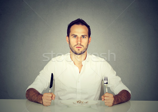 Man with fork and knife sitting at table with empty plate  Stock photo © ichiosea