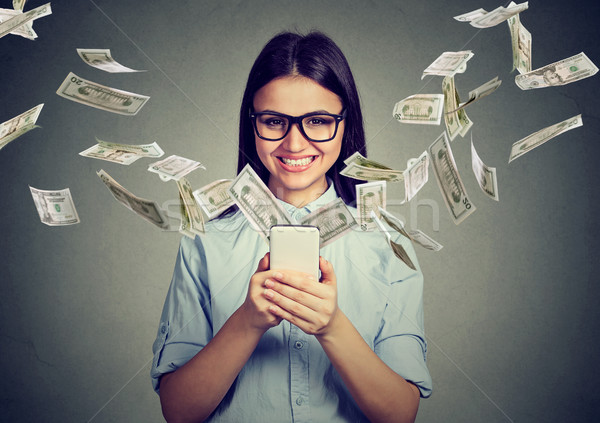 Stock photo: Happy woman in glasses using smartphone with dollar bills flying away