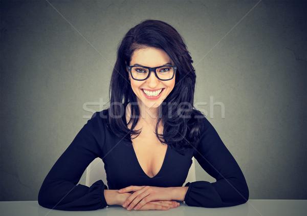 ストックフォト: 笑みを浮かべて · ビジネス女性 · 座って · 表 · 見える · カメラ