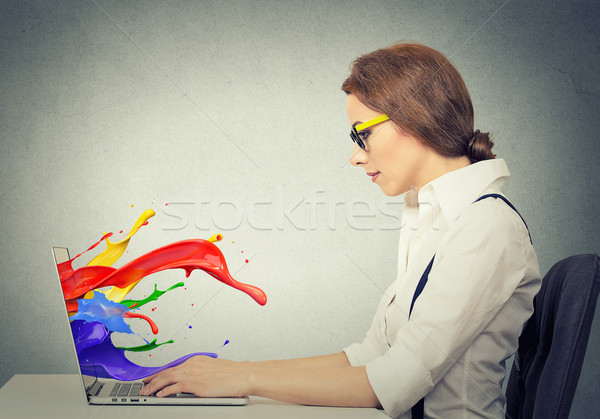 woman working on computer colorful splashes coming out of screen Stock photo © ichiosea