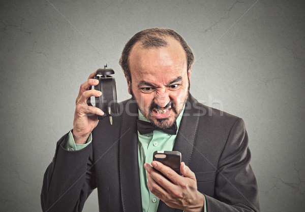 angry businessman with alarm clock looking at smartphone Stock photo © ichiosea