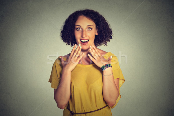 Stock photo: happy woman looking excited, surprised in full disbelief, hands on chest, it's me?