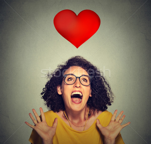 portrait super excited funky girl in love looking up at red heart  Stock photo © ichiosea