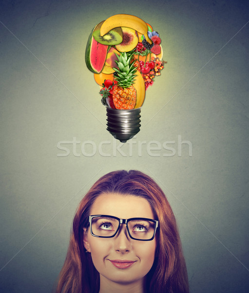 Eating healthy diet tips concept. Woman looking up at fruits light bulb  Stock photo © ichiosea