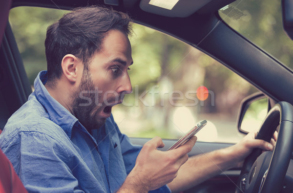 Stock photo: Man sitting inside car with mobile phone texting while driving