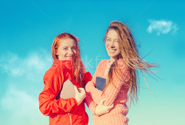 Two attractive girls having fun outdoors enjoying fresh air on windy summer day   Stock photo © ichiosea