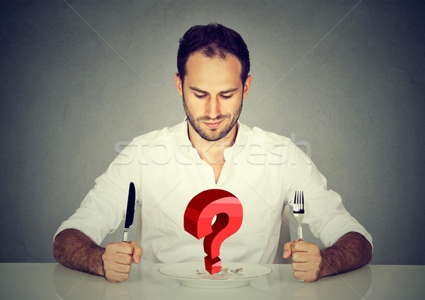 Man with fork and knife sitting at table looking at plate with big red question  Stock photo © ichiosea