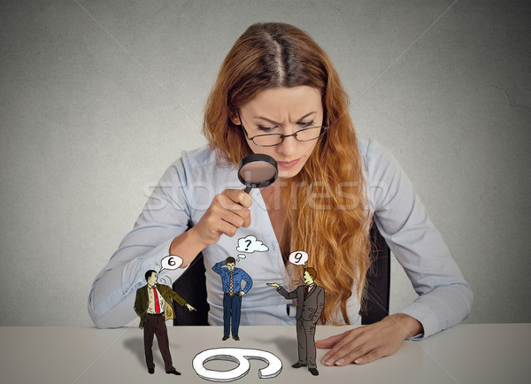 Businesswoman skeptically looking at arguing people through magnifying glass Stock photo © ichiosea