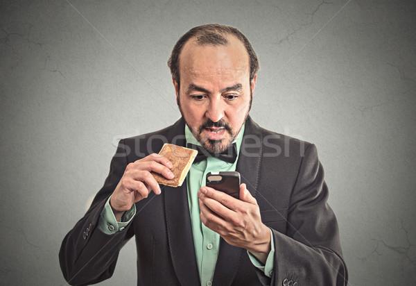 Sorpreso uomo d'affari mangiare cookie smartphone ritratto Foto d'archivio © ichiosea
