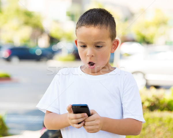 Surprised boy looking at his smart phone Stock photo © ichiosea