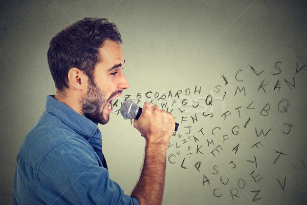 Young man singing in microphone with alphabet letters coming out of his mouth Stock photo © ichiosea