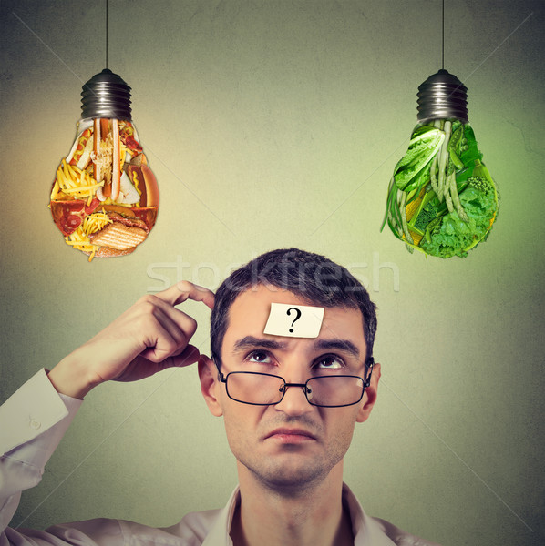 Man with question mark thinking looking up at junk food and vegetables shaped as light bulb Stock photo © ichiosea