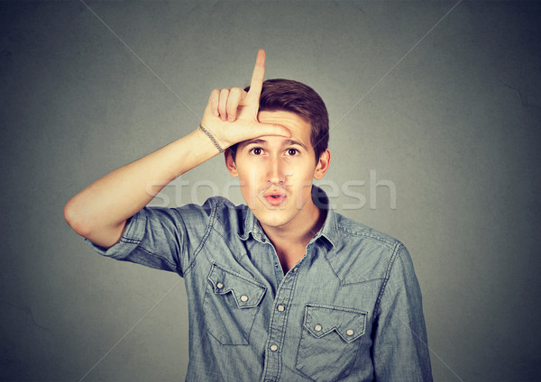 Young man showing loser sign on forehead, looking with disgust  Stock photo © ichiosea