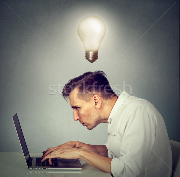 Stock photo: Side profile young man working on computer sitting at desk