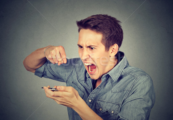 angry young man screaming on mobile phone i Stock photo © ichiosea
