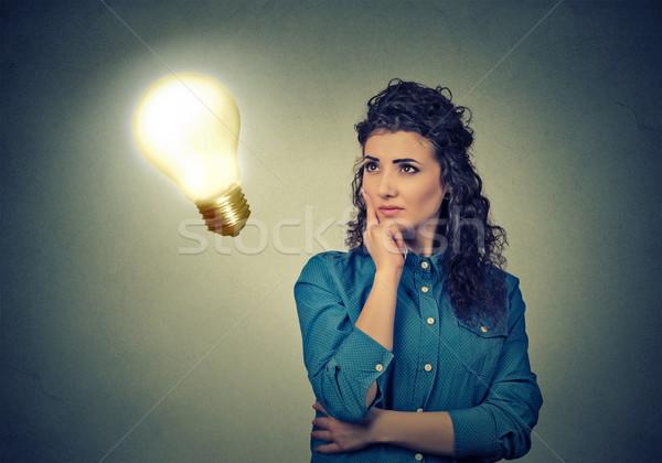 Woman thinking dreaming looking up at bright light bulb Stock photo © ichiosea