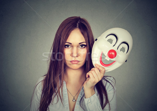 Upset worried woman with sad expression taking off clown mask  Stock photo © ichiosea