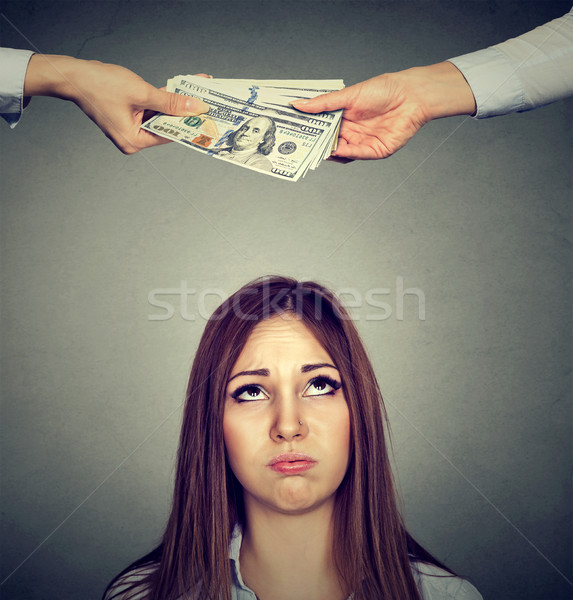 worried sad woman looking up at two hands exchanging money Stock photo © ichiosea