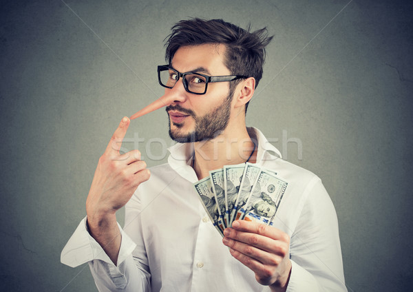 Financial fraud. Liar businessman with dollar cash  Stock photo © ichiosea