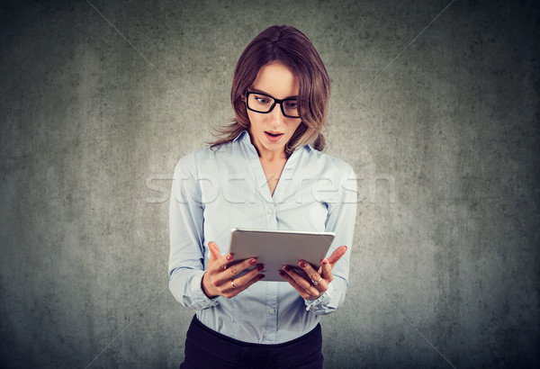 stunned woman, surprised with wide open mouth, shocked by what she sees on her tablet Stock photo © ichiosea