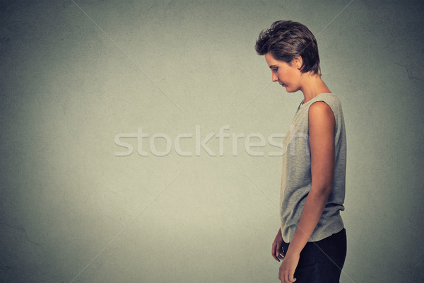 Side profile sad lonely young woman standing looking down Stock photo © ichiosea
