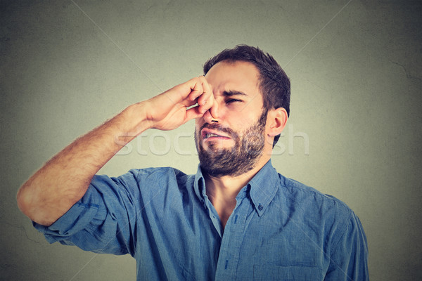 disgusted man pinches nose with fingers hands looks with disgust something stinks  Stock photo © ichiosea