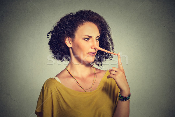 Stock photo: Woman with long nose isolated on grey wall background. Liar concept.
