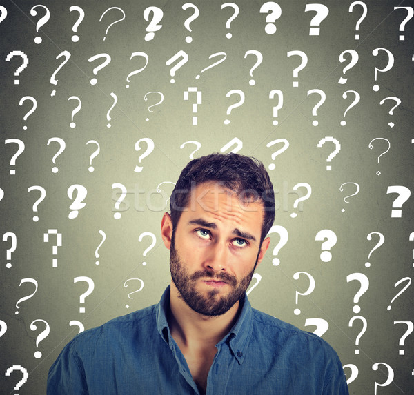 funny confused skeptical man thinking looking up has many questions  Stock photo © ichiosea