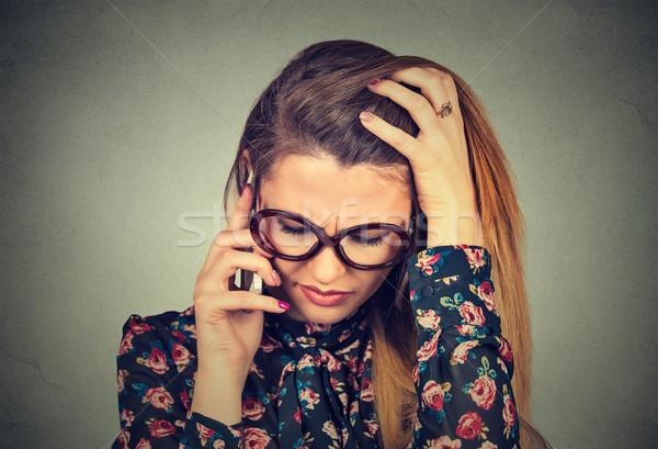 Mutsuz umutsuz genç kadın konuşma cep telefonu aşağı bakıyor Stok fotoğraf © ichiosea