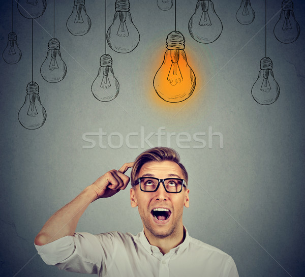 Man in glasses looking up at light bulb has solution  Stock photo © ichiosea