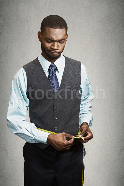 Unhappy businessman measuring his waist line. Stock photo © ichiosea