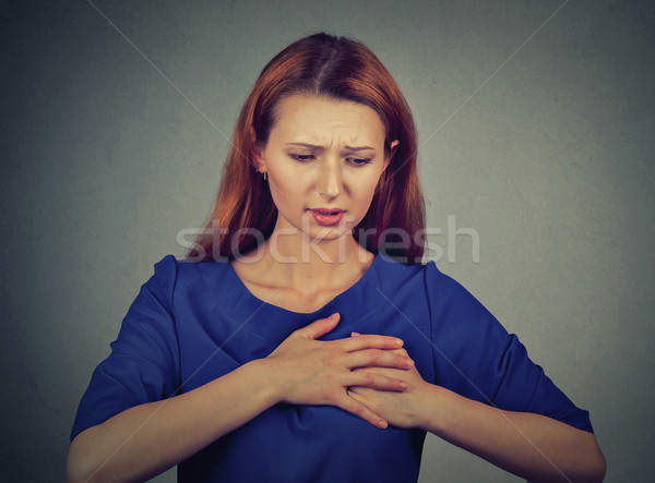 young woman with breast pain touching chest isolated on gray wall background Stock photo © ichiosea