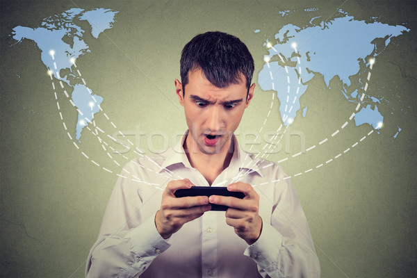 Surprised man holding smartphone connected browsing internet  Stock photo © ichiosea