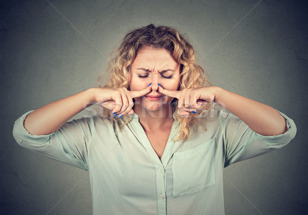 woman pinches nose with fingers looks with disgust something stinks Stock photo © ichiosea