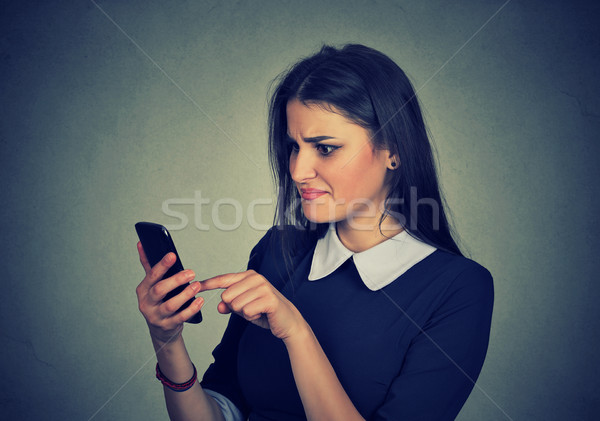 Confused upset woman looking at her mobile phone  Stock photo © ichiosea