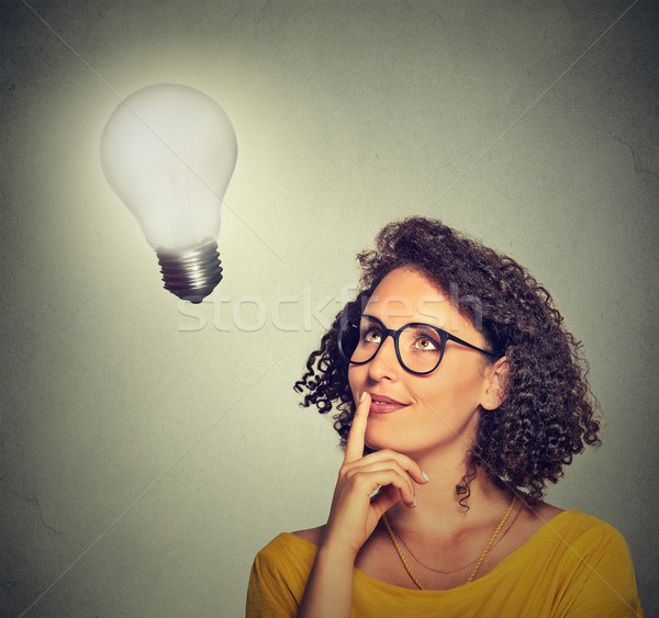 woman thinks looking up at bright light bulb Stock photo © ichiosea