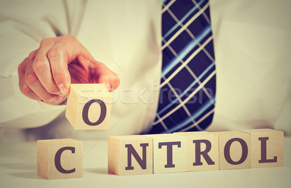 business man hand arranging wooden cubes reading control on a table Stock photo © ichiosea