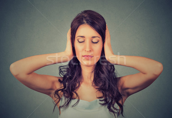 Relaxed woman with eyes closed covering her ears with hands  Stock photo © ichiosea