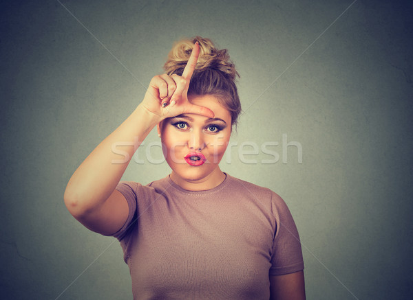 Stock photo: unhappy woman giving loser sign on forehead, looking at you, disgust on face