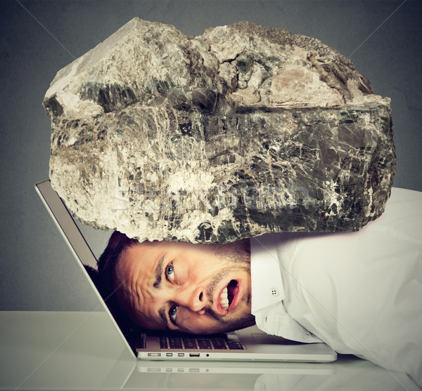 Stressed business man with head squeezed between laptop and rock Stock photo © ichiosea