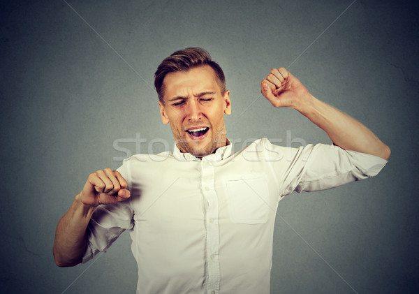 Young sleepy man yawning stretching arms back  Stock photo © ichiosea
