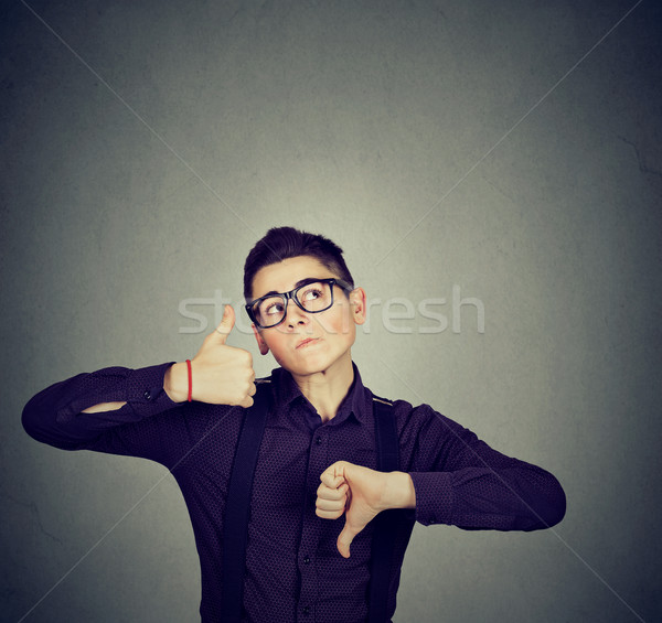 Stock photo: Perplexed man with thumbs down thumbs up gesture looking up