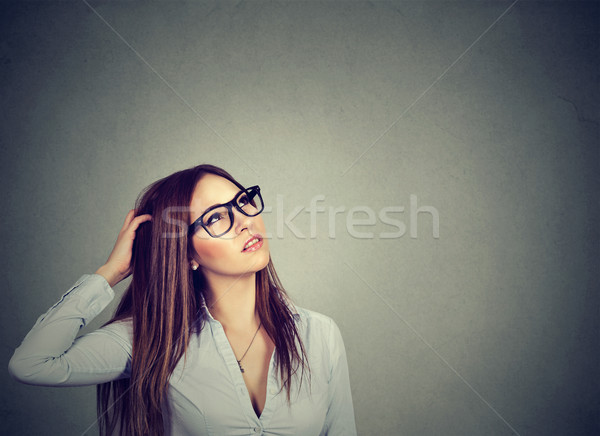 Thoughtful pondering woman in eyeglasses scratching head perplexed  Stock photo © ichiosea