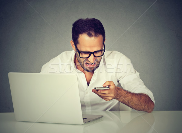 Angry man having problems on line with a laptop talking on mobile phone with support service  Stock photo © ichiosea
