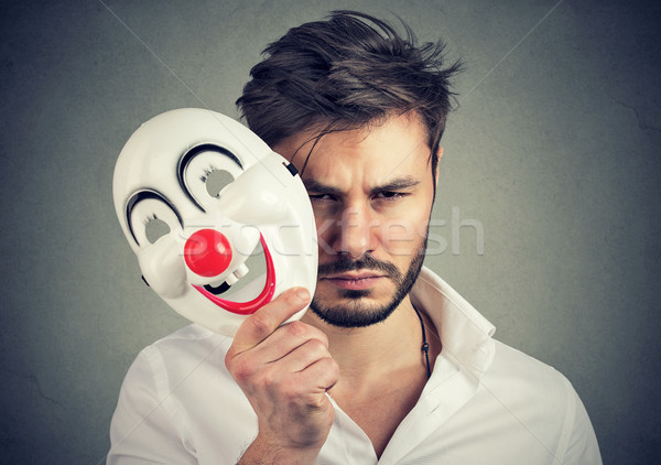Unhappy man covering feelings with mask Stock photo © ichiosea