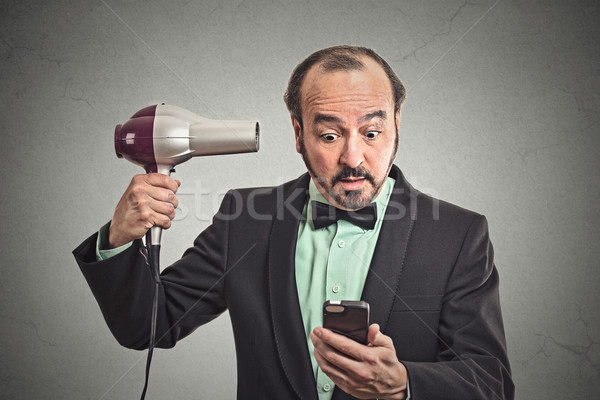 business man reading news on smartphone holding hairdryer Stock photo © ichiosea