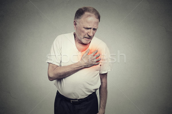 Stock photo: senior man suffering from bad pain in his chest heart attack