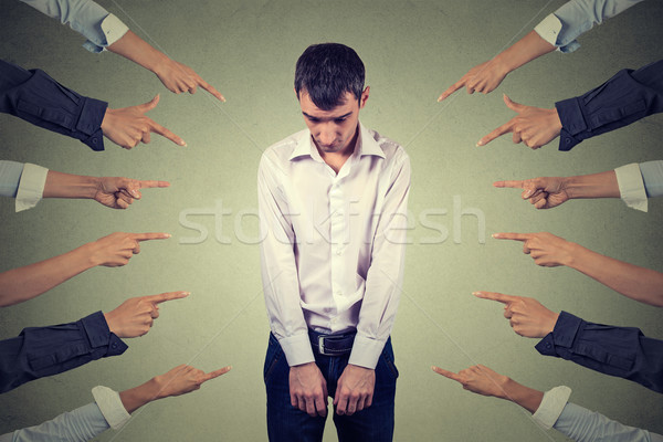 accusation of guilty guy. Sad upset man looking down many fingers pointing at him Stock photo © ichiosea