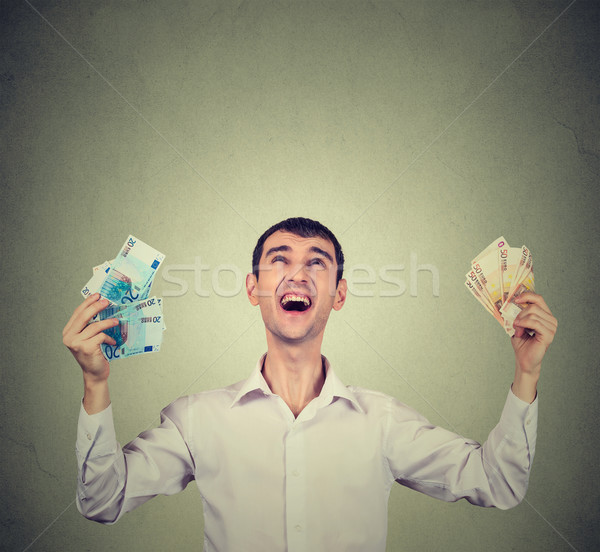 Portrait happy man ecstatic celebrates success holding money euro bills banknotes Stock photo © ichiosea
