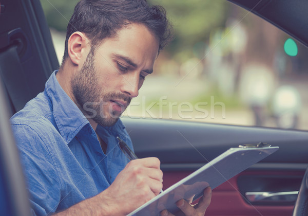 transportation ownership concept. Man inside new car reading signing documents Stock photo © ichiosea